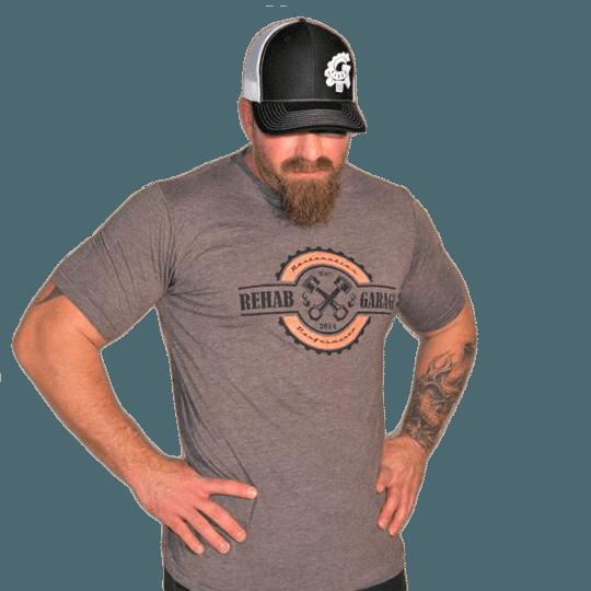 Rehab Garage grey t-shirt, wearing a black hat transparent background